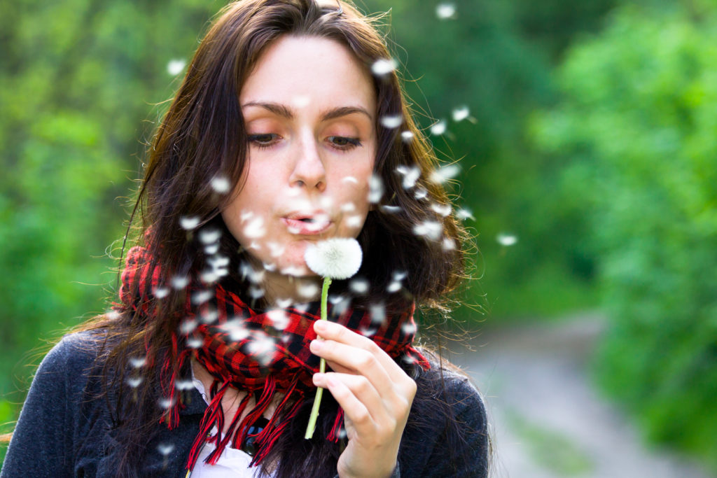 a woman blowing on a dandilion while traveling with allergies