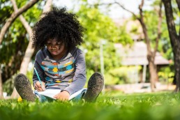 Child Reading In Grass
